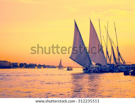 Feluccas at sunset - traditional sail vessel on Nile river in Egypt. Silhouettes of egyptian sail boats - shoreline on the Nile in evening. - stock photo