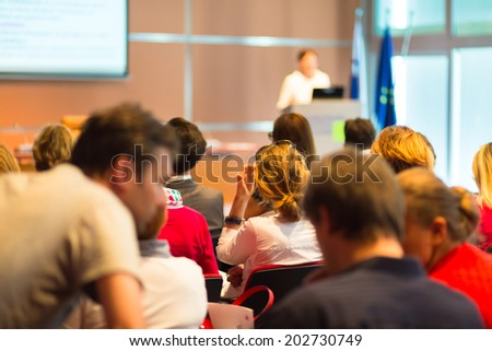 Female academic professor lecturing at faculty. Students at the lecture hall. - stock photo