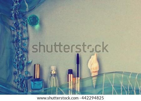 female accessories, nail polish, scarf, mascara, perfume, beads, seashell on cardboard textured surface, turquoise toned style - stock photo