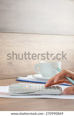 Female accountant doing a calculation on a  manual calculator with a cup of coffee in background, side view. - stock photo