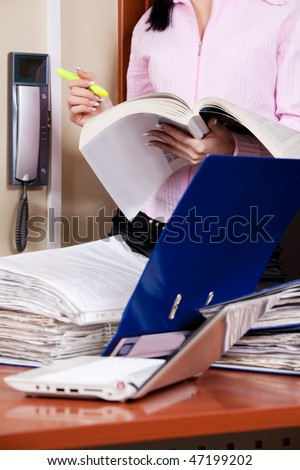 Female accountant with desk overloaded with papers in front - stock photo