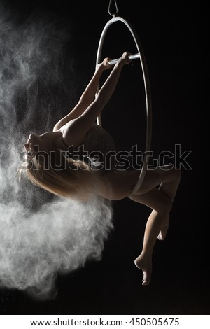 Female acrobat doing element on aerial hoop with sprinkled flour - stock photo