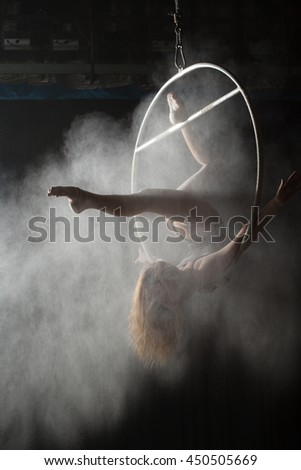 Female acrobat doing gymnastic element on aerial hoop with sprinkled flour - stock photo