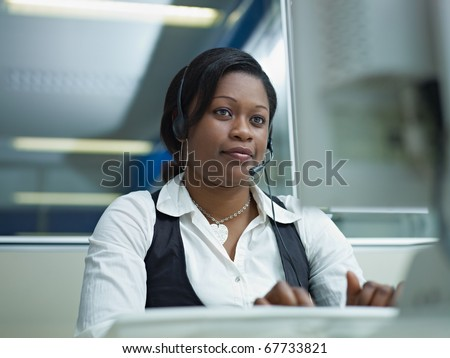 female african american customer service representative talking on the phone and typing on pc. Horizontal shape, front view - stock photo
