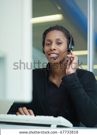 female african american customer service representative with headset looking at camera and smiling. Verical shape, front view, waist up - stock photo