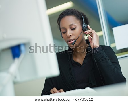 female african american customer service representative with headset typing on computer. Horizontal shape, front view, waist up - stock photo
