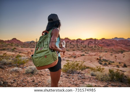 female african american hiker watching sunset in nevada desert at valley of fire