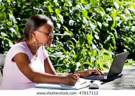 female African American student studying outdoors - stock photo