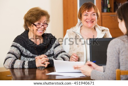 Female agent consulting cheerful elderly women in office  - stock photo