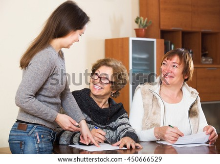 Female agent consulting smiling mature women in office