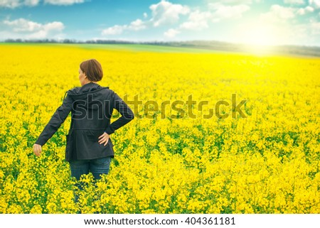 Female agricultural expert controlling the growth of cultivated rapeseed crops.