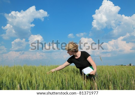 Female agricultural expert inspecting quality of wheat