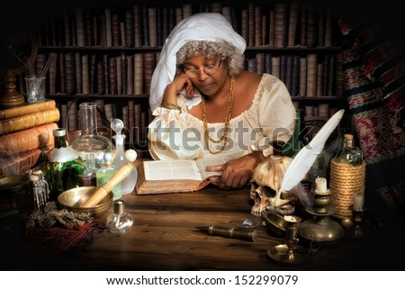 Female alchemist studying in her books at night - stock photo
