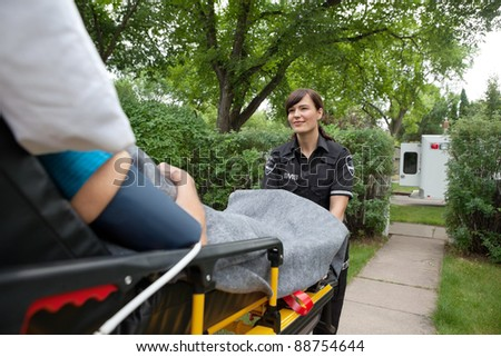 Female ambulance worker transporting elderly patient from home to hospital - stock photo