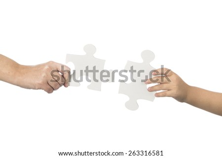 Female and child hand with jigsaw - stock photo