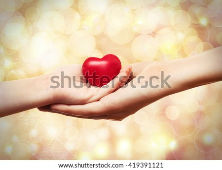 Female and child hands holding red heart on blurred background. Family, love and health care concept