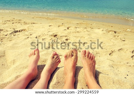 Female and children's feet on a beach against the sea in a summer sunny day. Family rest - stock photo