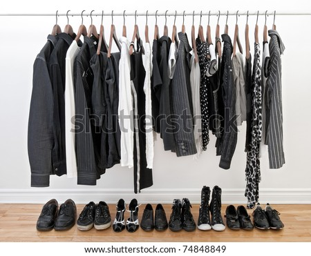 Female and male black and white clothes on a rod and shoes on a wooden floor. - stock photo