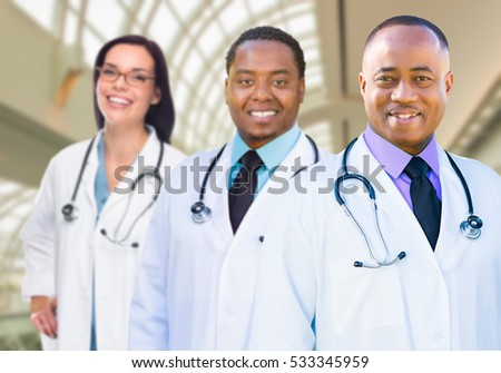 Female and Male Caucasian and African American Doctors in Hospital Office.