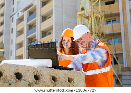 female and male construction workers looking at laptop - stock photo