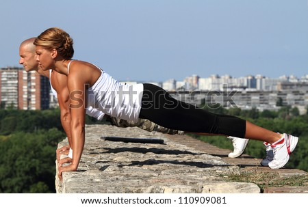 Female and male fitness instructors doing pushups on the top of the stone wall. - stock photo