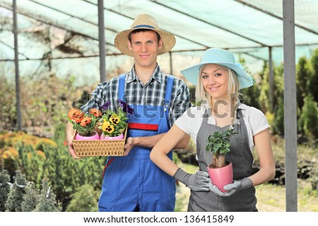 Female and male gardeners holding flower pots and posing in a hothouse - stock photo
