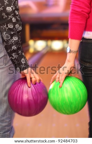 Female and male hands holding balls before throwing in bowling club - stock photo