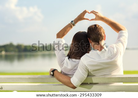 female and male hands making up heart shape over blue sky  - stock photo