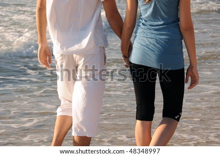 Female and male holding hands on a background of sea