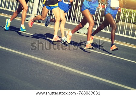 Female And Male Marathon Runners Running On City Road