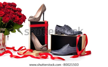 Female and male shoes on gift boxes and bunch of roses over white background - stock photo