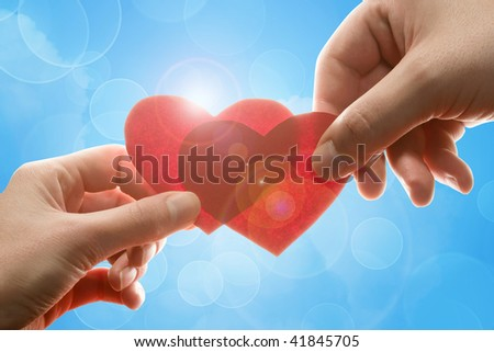 Female and man's hands with red hearts - stock photo