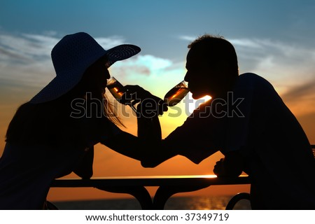 Female and man's silhouettes on sunset behind table drink from glasses - stock photo