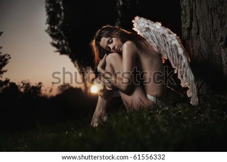 Female angel posing over an autumn sunset - stock photo