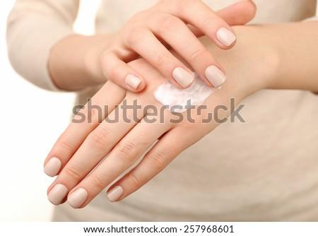 Female applying cream on her hand, closeup - stock photo
