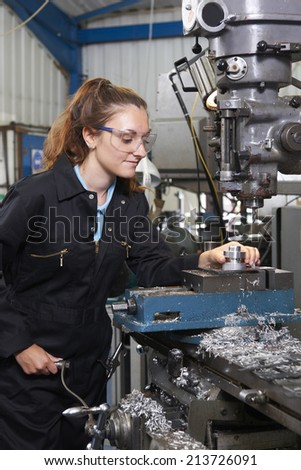 Female Apprentice Engineer Working On Drill In Factory - stock photo