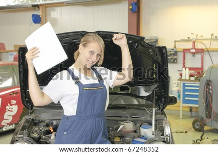 Female apprentice to mechanic has passed the exam and is happy in the Workshop front of a car - stock photo