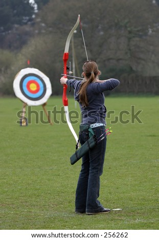Female archer aiming at target - stock photo