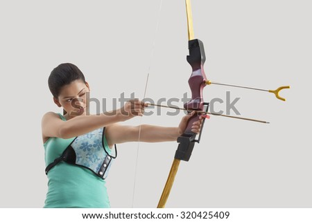 Female archer practicing archery against gray background
