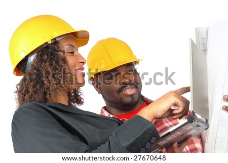 Female architect and construction worker looking at laptop together - stock photo