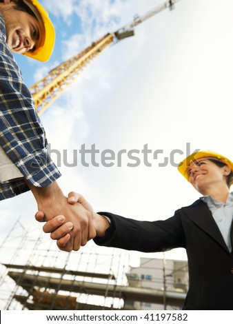 female architect and construction worker shaking hands. Low angle view, copy space - stock photo