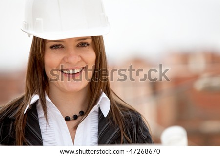 Female architect at a construction site and smiling - stock photo