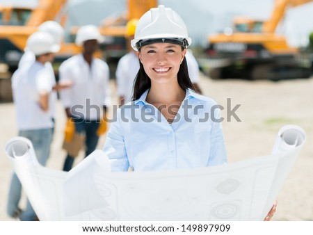 Female architect at a construction site holding blueprints  - stock photo