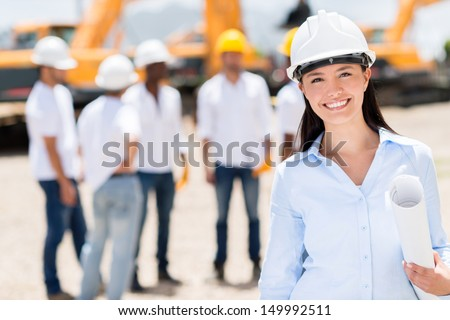 Female architect at a construction site looking happy - stock photo