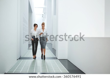 Female architect browse wireless on cell telephone while her partner comes near with touch pad in hands, young businesswomen chat on mobile phone while walking in office interior with digital tablet - stock photo