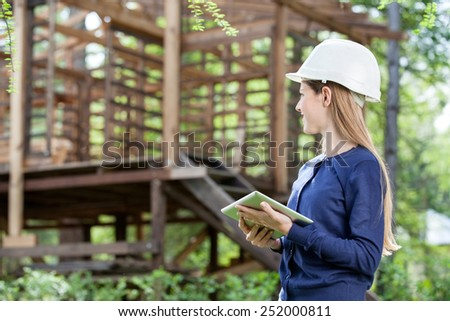 Female architect holding digital tablet while looking at incomplete timber cabin at construction site - stock photo