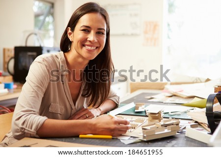 Female Architect Making Model In Office - stock photo