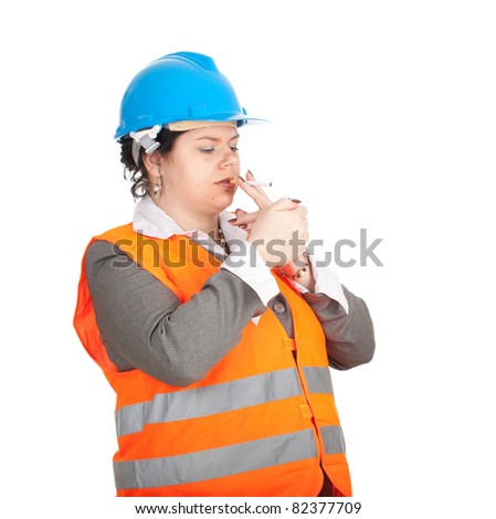 female architect or engineer in orange protective waistcoat and blue helmet  preparing to smoking cigarette - stock photo