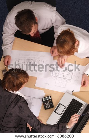 female architect showing bluepronts to the couple in the office - stock photo