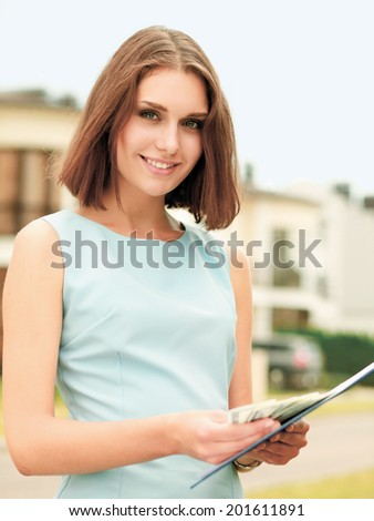 Female architect standing with folder and money - stock photo
